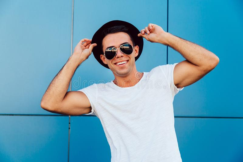 Handsome man in sunglasses and hat posing at camera outdoors royalty free stock images