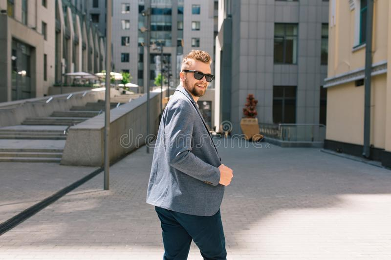 Handsome man in sunglasses walking on street on office building background. He wears T-shirt, jacket, jeans, beard. H royalty free stock image