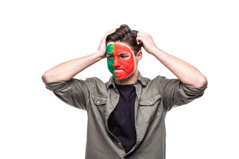 Handsome man supporter fan of Portugal national team painted flag face get unhappy sad frustrated emoitions into a camera. Fans em stock image