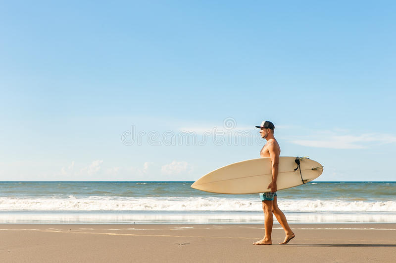 Handsome man with surfing board on spot. stock photos