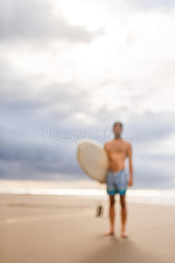Handsome man with surfing board on spot. stock photography