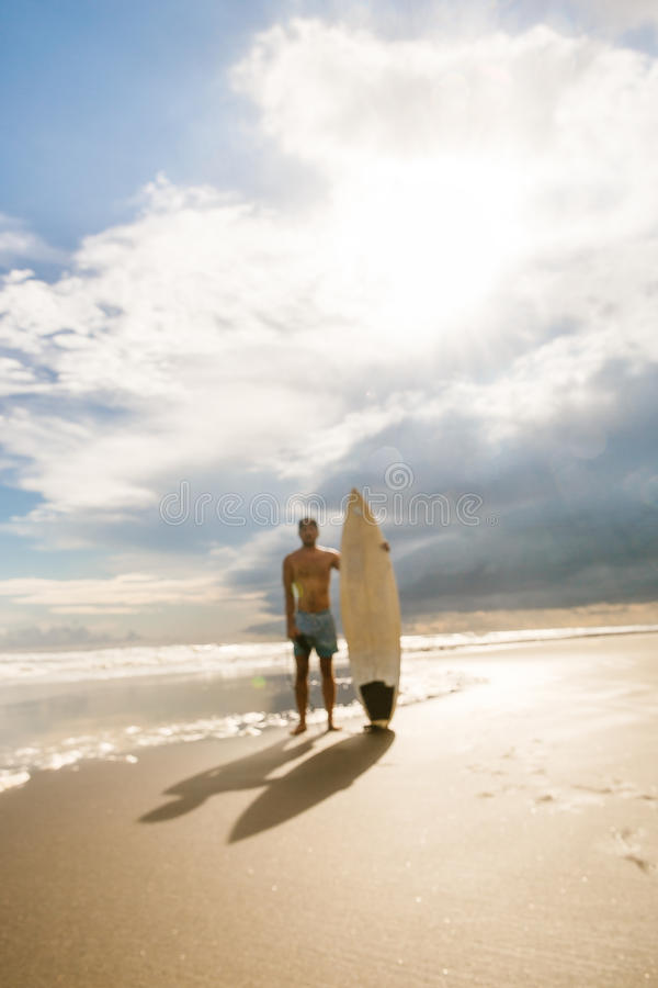 Handsome man with surfing board on spot. royalty free stock photography