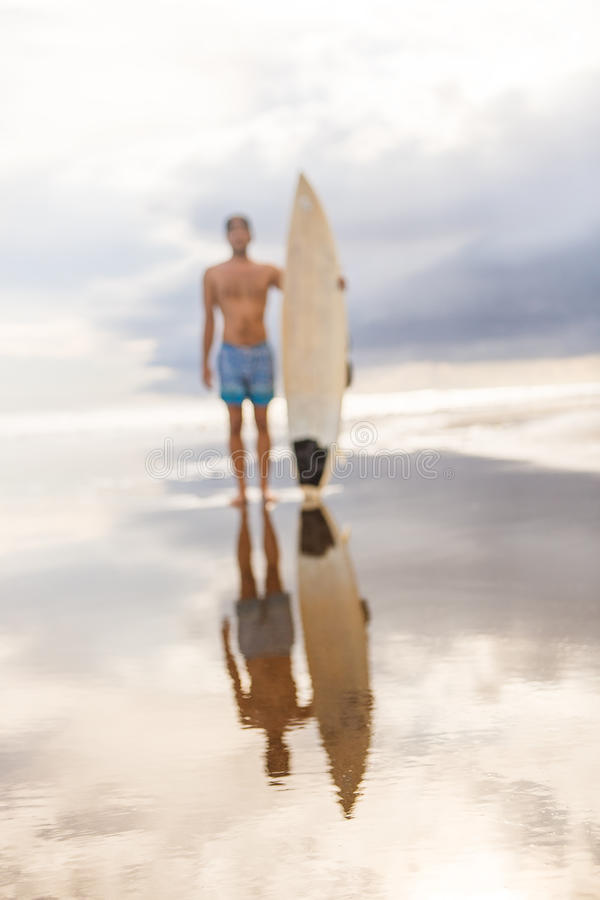 Handsome man with surfing board on spot. stock images