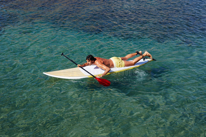 Handsome man swimming on a surfboard at the clear water royalty free stock image