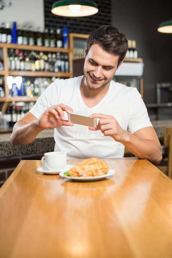 Handsome man taking a picture of his sandwich. In a pub stock photos