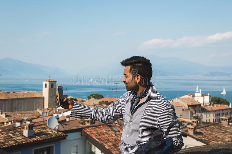 Handsome man taking a selfie. Handsome Indian man taking a selfie in a vacation context. Street fashion and style royalty free stock image