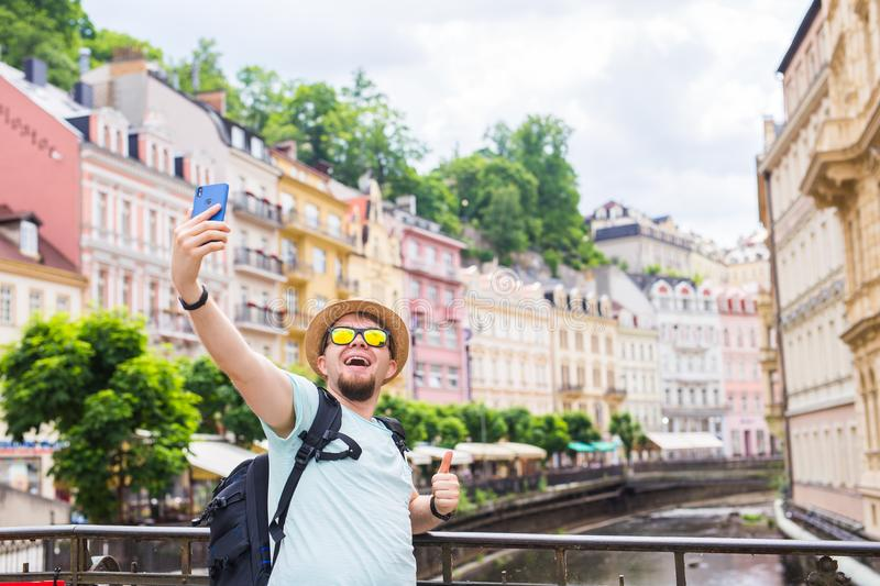Handsome man taking selfie with mobile smart phone camera in european city. Vacation, travel and holiday concept. royalty free stock photography