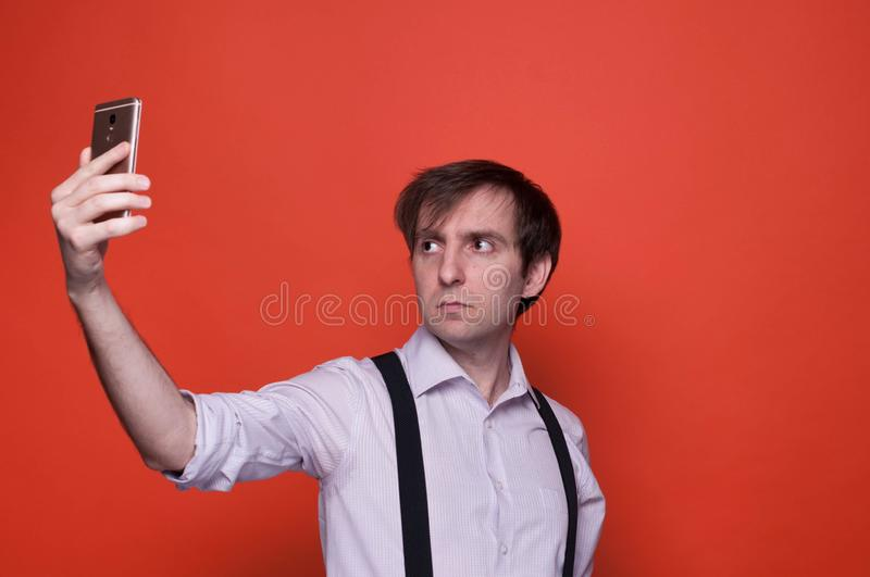 Handsome man taking selfie on orange background. Serious handsome man in shirt with rolled up sleeves and black suspender standing and taking selfie on orange stock photo