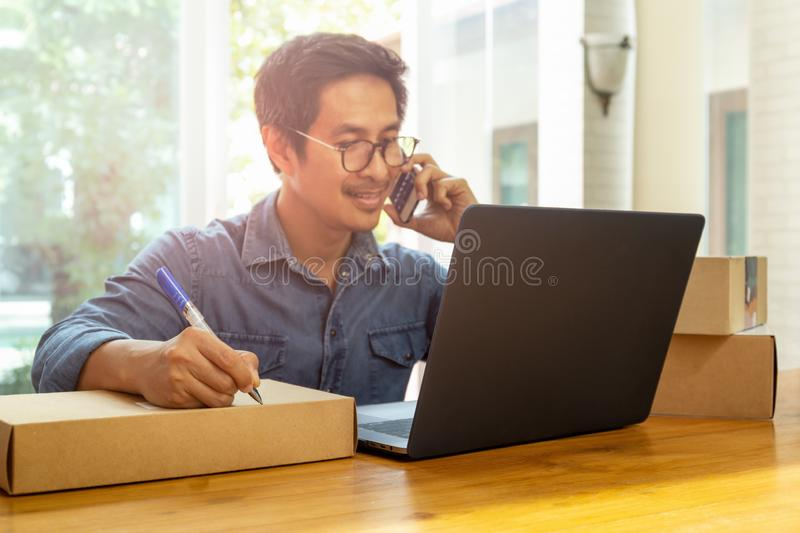 Handsome man talking on cell phone with hand writing on parcel. stock images