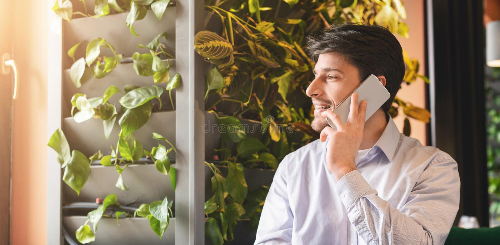 Handsome man talking on phone and smiling at modern cafe royalty free stock image