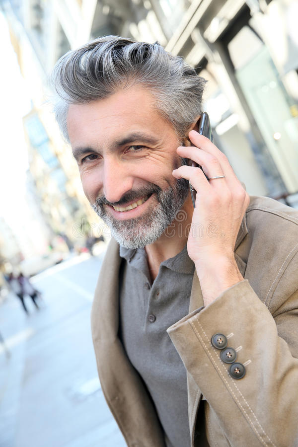 Handsome man talking on the phone in the street royalty free stock photography