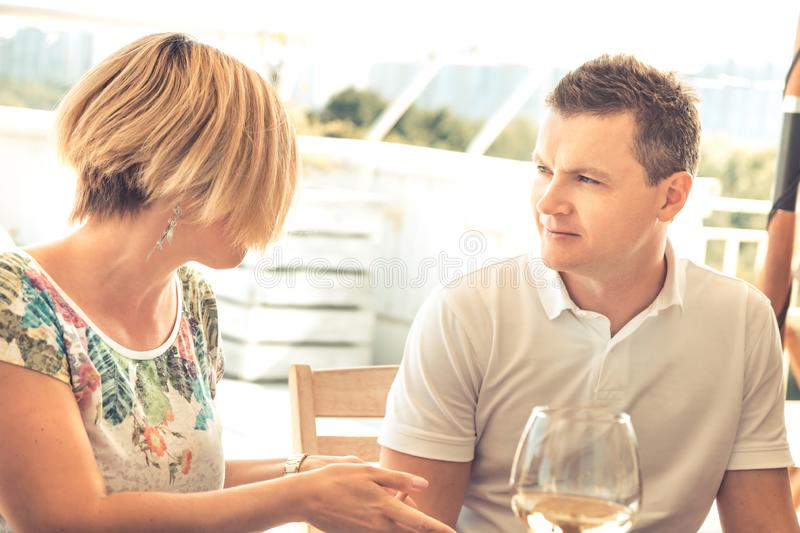 Handsome man talking with woman in cafe in sunny day with warm light during travel holidays concept couple marriage. Handsome men talking with unrecognizable royalty free stock images