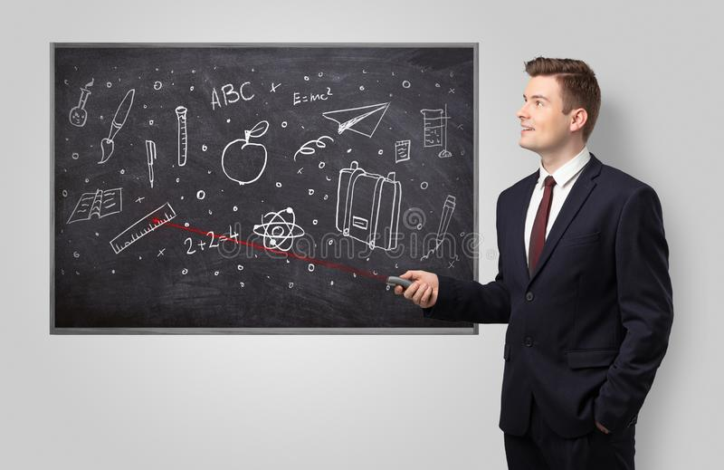 Handsome man teaching in classroom stock image