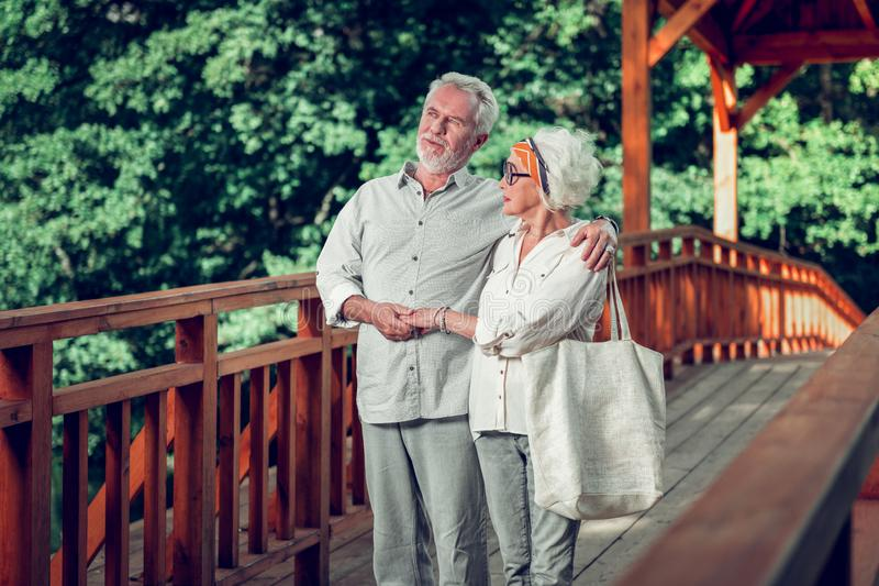 Handsome man tenderly hugging the charming aging beautiful alluring wife royalty free stock photography