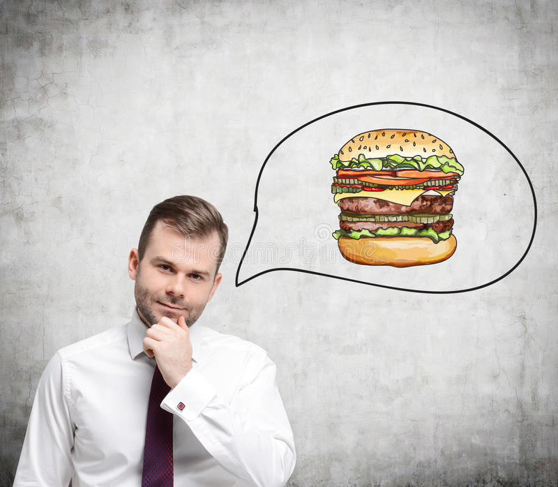 A handsome man is thinking about burger. A fast food concept. Concrete background royalty free stock photos