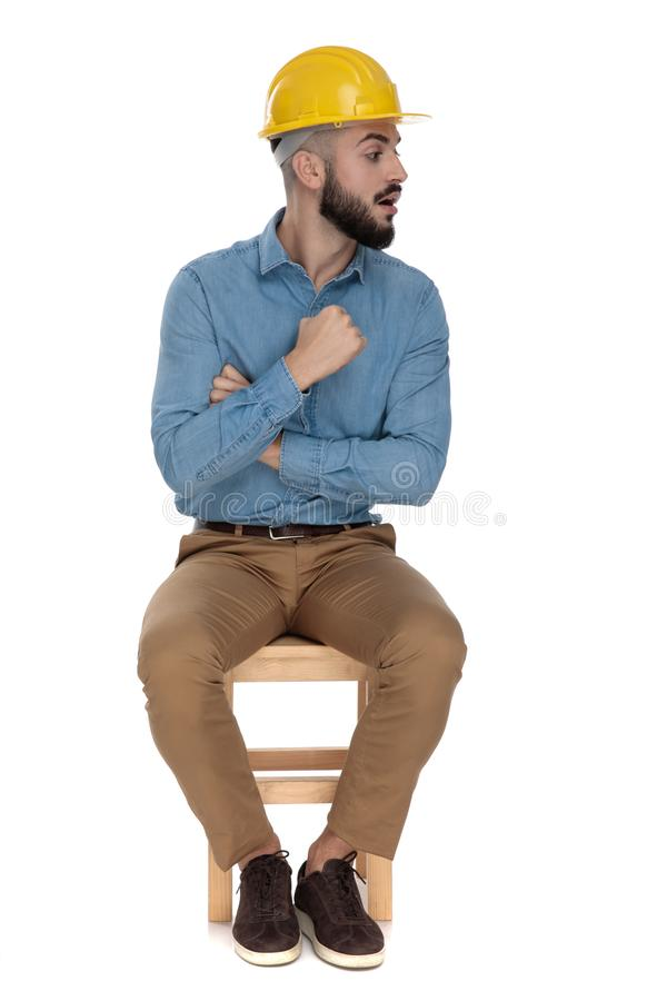Handsome man threatening with fist while sitting with arms folded. Handsome man with yellow safety helmet threatening with fist while sitting with arms folded on stock photography
