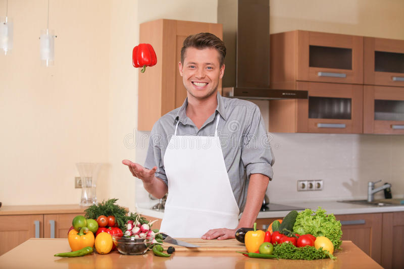 Handsome man throwing pepper into air. Guy preparing food at kitchen counter stock images