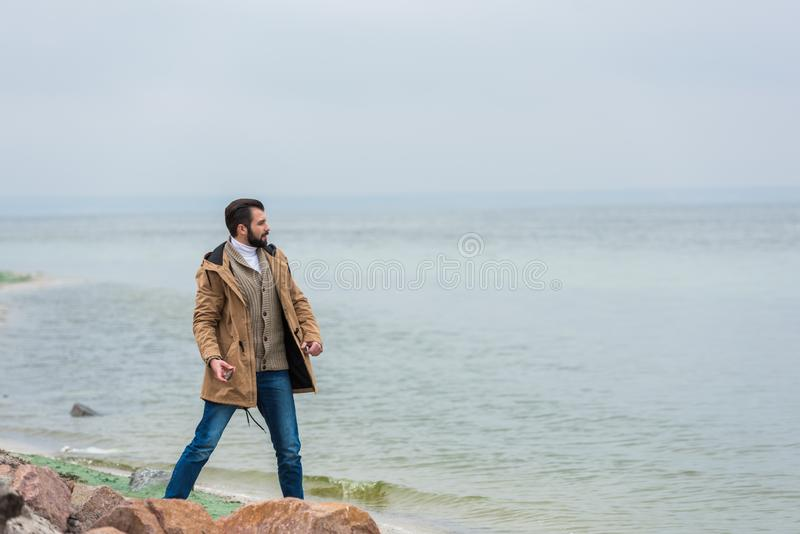 handsome man throwing stones into sea on cloudy royalty free stock photo