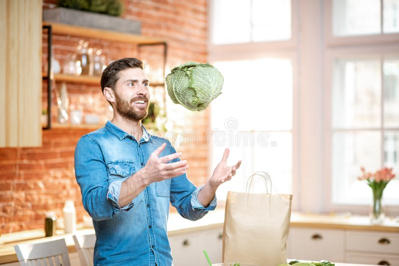 Man cooking vegan meals on the kitchen. Handsome man throwing up cabbage head while cooking vegan meals on the kitchen at home stock image