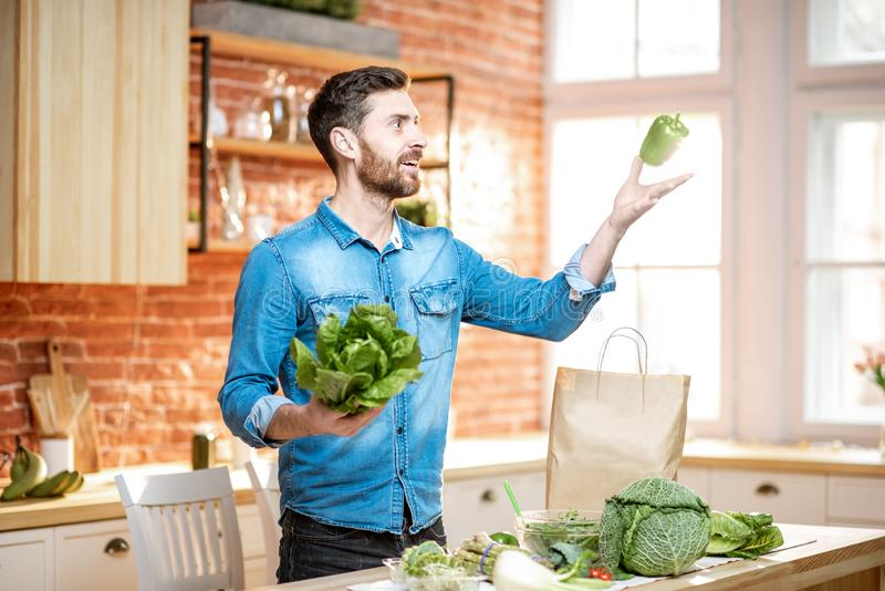 Man cooking vegan meals on the kitchen. Handsome man throwing up green pepper while cooking vegan meals on the kitchen at home royalty free stock images