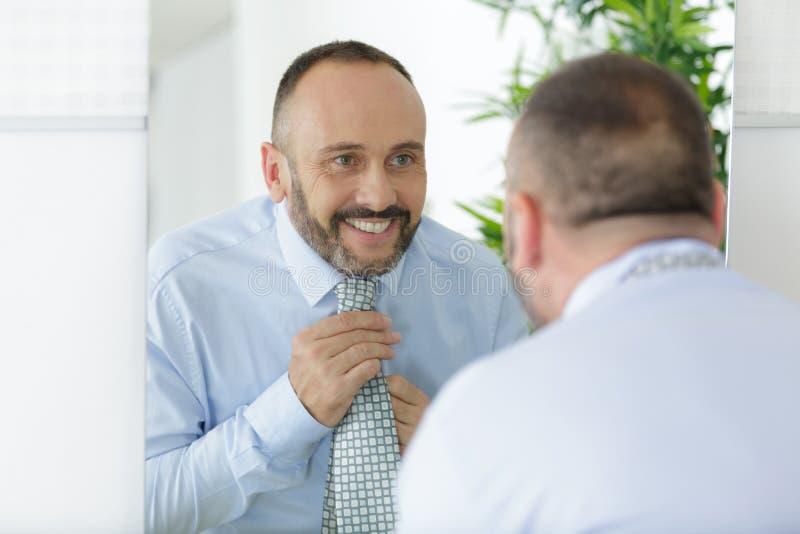 Handsome man ties up tie in front mirror stock photos