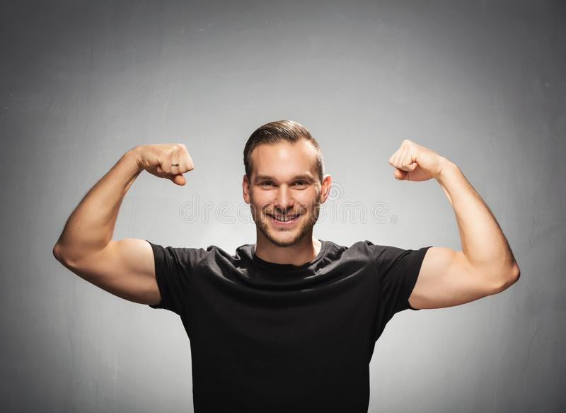 Handsome man tightening his muscles. Power gesture. stock photo