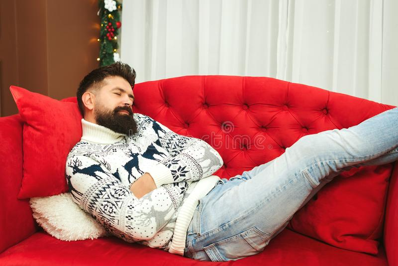 Handsome man tired while preparation christmas gifts. Christmas holidays. Young father sleeping at modern sofa in living room. After xmas celebration. Christmas stock photos