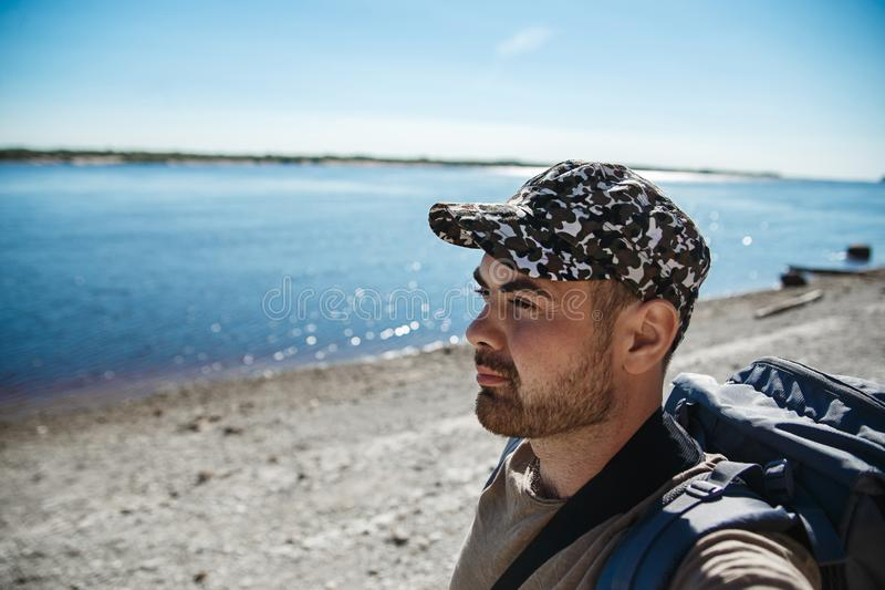 Handsome man tourist with backpack looking to beautiful river in hot summer day stock image
