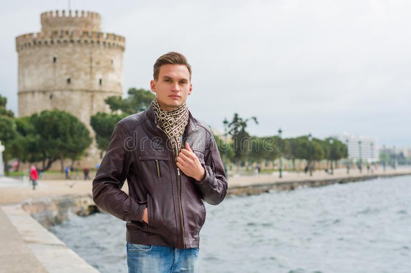 Handsome man, tourist, stands near a White Tower in the center Thessaloniki, Greece in front of a sea royalty free stock images