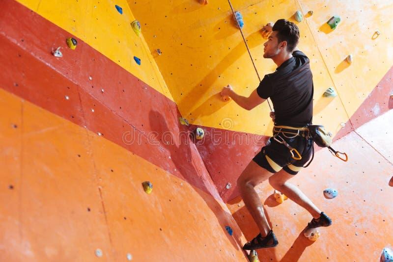 Handsome man training hard in climbing gym stock image