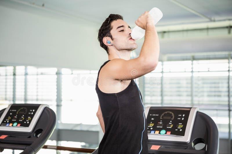 handsome man on treadmill drinking water stock photo