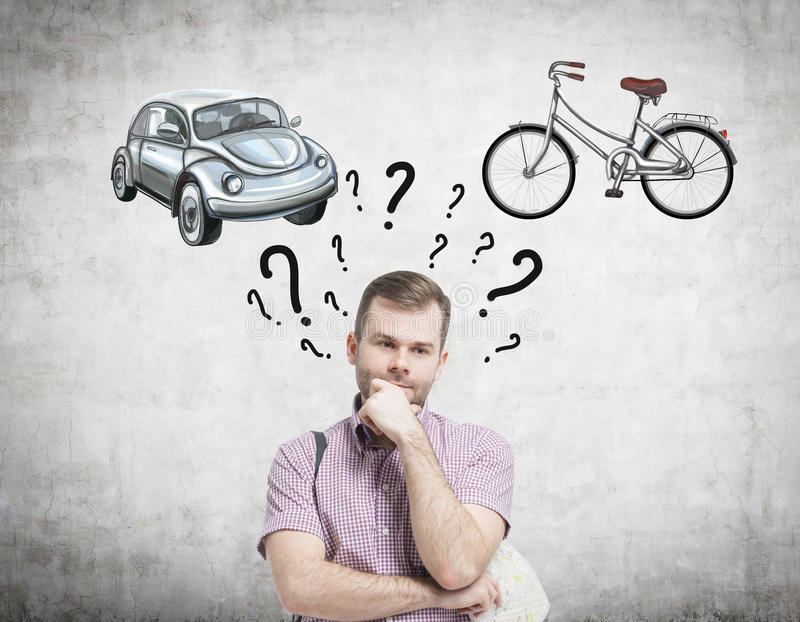 A handsome man is trying to chose the most suitable way for travelling or commuting. Two sketches of a car and a bicycle are drawn. On the concrete wall royalty free stock image