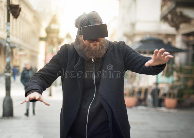Handsome man using high tech virtual reality glasses outdoor stock photos