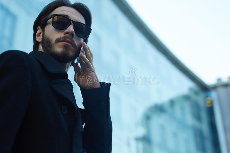 Handsome Man Using Phone in Streets of City. Low angle portrait of handsome modern man wearing sunglasses and black coat making phone call outdoors in streets of royalty free stock photography