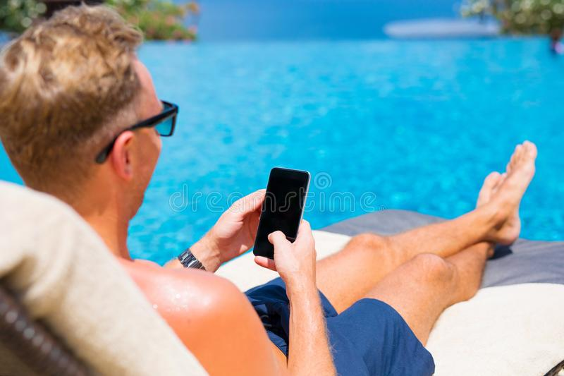 Man using smartphone by the pool. stock images