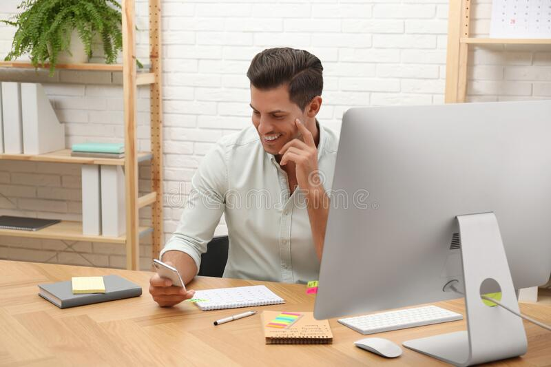 Handsome man using smartphone while working with calendar at table in office royalty free stock photos
