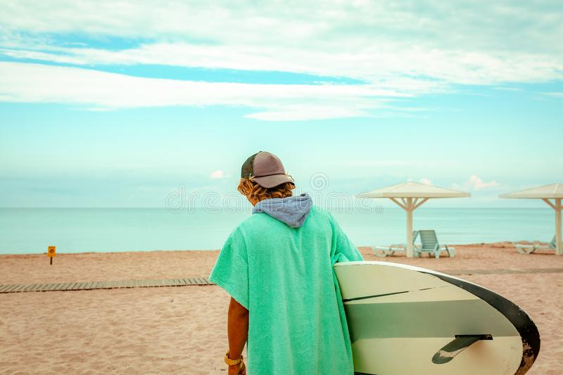 Handsome man walk with white blank surfing board wait for wave to surf spot at sea ocean shore. Back View. Concept of stock photo
