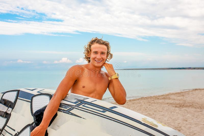 Handsome man walk with white blank surfing board wait for wave to surf spot at sea ocean shore. Concept of sport royalty free stock photography