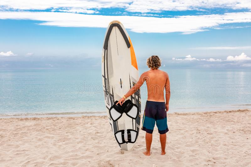 Handsome man walk with white blank surfing board wait for wave to surf spot at sea ocean shore. Concept of sport royalty free stock photos