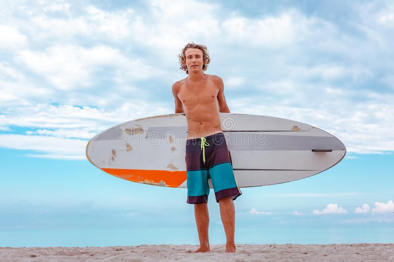 Handsome man walk with white blank surfing board wait for wave to surf spot at sea ocean shore. Concept of sport stock photos