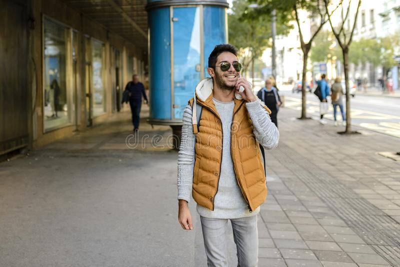 Handsome man walking with the phone royalty free stock image
