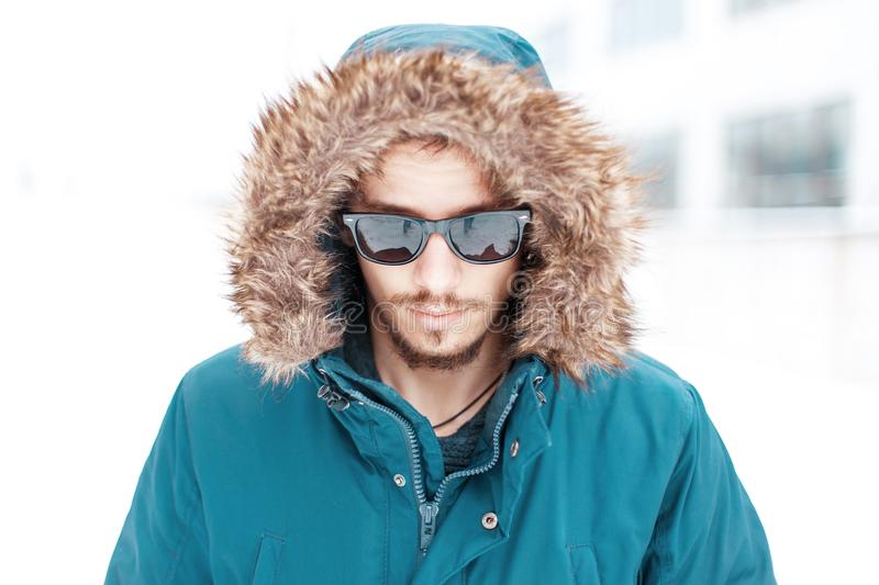 Handsome man in warm winter jacket with fur hood and sunglasses royalty free stock photography
