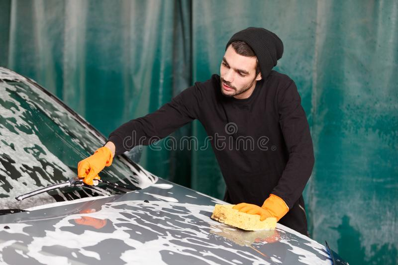 A handsome man is washing a car stock photo
