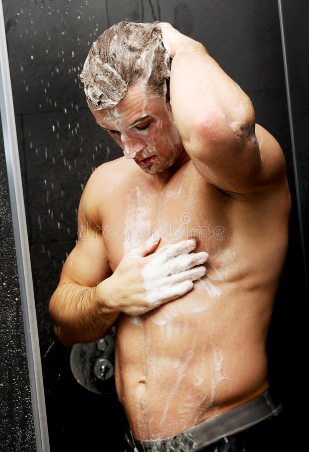 Handsome man washing himself with soap. royalty free stock images