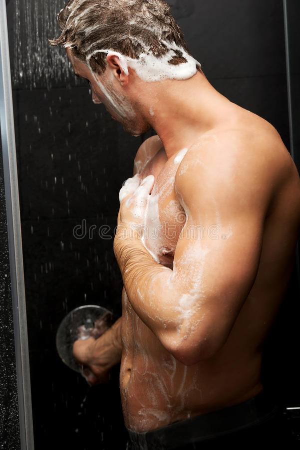 Handsome man washing himself with soap. royalty free stock photo