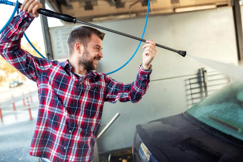 Handsome man washing his car using only a spray gun royalty free stock photos