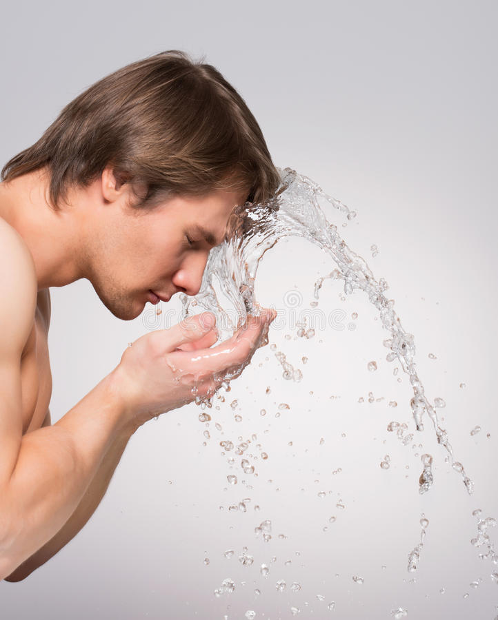 Handsome man washing his clean face. royalty free stock photography