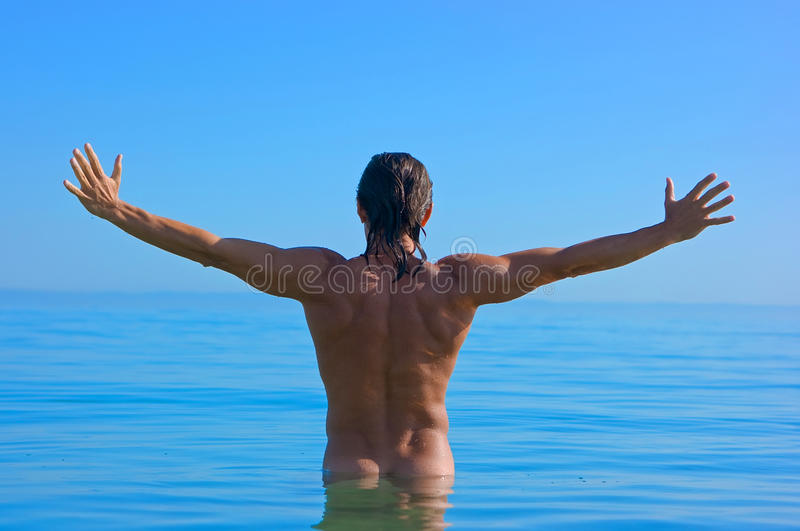 Handsome man in water stock photography