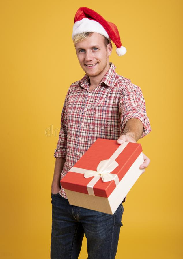 Handsome man wear santa hat holding a lot of gift box on yellow stock photo