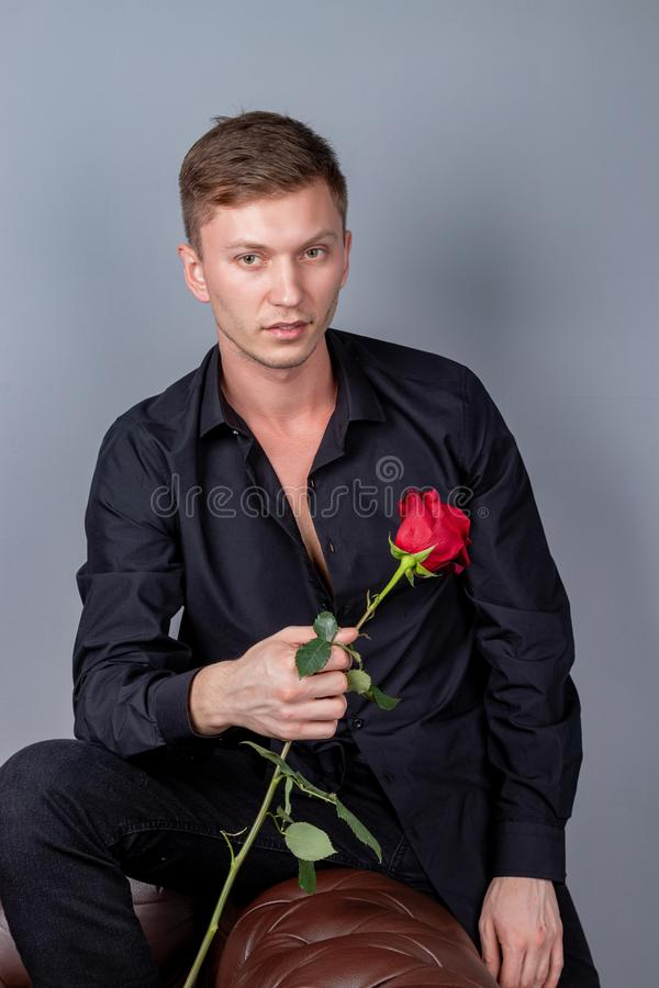 Handsome man wearing black shirt sitting on the leather sofa holding a rose and getting ready romantic date. Handsome man wearing black shirt sitting on the stock photography